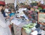 لاہور: شہری مال روڈ پر مسجد شہداء کے باہر ٹوپی خریدنے کے لیے پسند کر ..