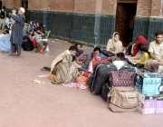 لاہور: ریلوے اسٹیشن پر مسافر پلیٹ فارم پر ٹرین کے انتظار میں بیٹھے ہیں۔