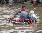 فیصل آباد: بارش کے بعد جمع ہونے والے پانی میں ایک موٹر سائیکل سوار فیملی ..