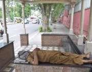 لاہور: مال روڈ پر بنے بس سٹاپ میں ایک شخص دوپہر کے وقت نیند پوری کر رہا ..
