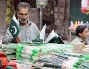 لاہور: اردوبازار میں ایک شخص جشن آزاد کے حوالے سے اشیاء کا سٹال سجا ..