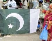 لاہور:اردو بازار میں ایک خاتون قومی پرچم خریدنے کے لیے پسند کر رہی ہے۔