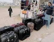 راولپنڈی: محنت کش رو ڈ کنارے سوٹ کیس فروخت کے لیے سجارہا ہے۔