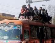 لاہور: نوجوان بس کی چھت پر سوار ہو کر سفر کر رہے ہیں، جو کسی حادثے کا ..