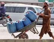 راولپنڈی: مزدور ہتھ ریڑھی پر پلاسٹک کے کین رکھے پانی بھرنے لیجا رہا ..