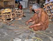 لاہور: ایک معمر محنت کش فروخت کے لیے ہاتھ سے فرنیچر بنا رہا ہے۔