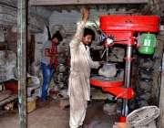 لاہور: محنت کش اپنی ورکشاپ میں ٹیوب ویل کے والو تیار کر رہا ہے۔