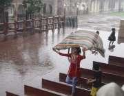 لاہور: شاہی قلعہ میں سیرو تفریح کے لیے آئی بچی بارش سے لطف اندوز ہو رہی ..