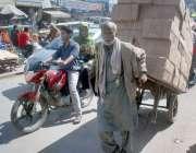 لاہور: ایک بزرگ محنت کش ہتھ ریڑھی پر بھاری سامان رکھ کر لیجا رہا ہے۔