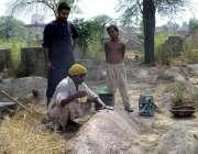 فیصل آباد: ایک شخص قبر پر مٹی کا لیپ کر رہا ہے۔