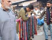 لاہور: ایک نوجوان سردی سے بچنے کے لیے مفرل خرید رہا ہے۔