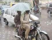 لاہور: شہر میں ہونیوالی بارش کے دوران موٹر سائیکل سوار چھتری تانے جار ..