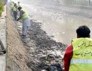 لاہور: محکمہ آب پاشی کے اہلکار لاہور کینال کی سالانہ بھل صفائی کے لیے ..
