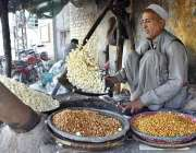 پشاور: دکاندار گاہکوں کو متوجہ کرنے کے لیے بھٹی پر چنے بھون رہا ہے۔