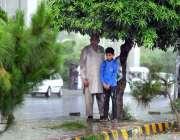 راولپنڈی: ایک معمر شخص سکول کے بچے کے ہمراہ بارش سے بچنے کے لیے درخت ..