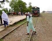چنیوٹ: ایک معمر شخص ریلوے ٹریک کراس کر رہا ہے جبکہ دوسری جانب سے ٹرین ..