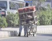 لاہور: ایک شخص دیسی مرغیاں فروخت کرنے کے لیے جار ہا ہے۔