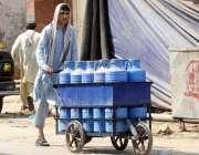 راولپنڈی: مزدور ہتھ ریڑھی پر پانی کے کین رکھے لیجا رہاہے۔