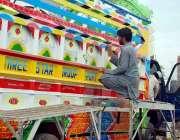 پشاور: ایک مزدور ٹرک پر پینٹنگ بنانے میں مصروف ہے۔