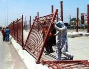 پشاور: مزدور حاجی کیمپ کے قریب سڑک کنارے لوہے کی باڑ لگانے میں مصرورف ..