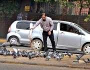 لاہور: نیشنل آرٹ کالج کے قریب شہری کبوتروں کو دانہ ڈال رہا ہے۔