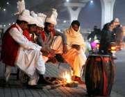 راولپنڈی: کام کے انتظار میں بیٹھے ڈھولچی سردی کی شدت سے بچنے کے لیے ..