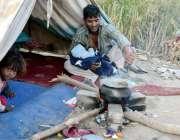 لاہور: خانہ بدوش شخص کھلے آسمان تلے کھانا تیار کررہا ہے۔