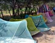 سرگودھا: ایک محنت کش سڑک کنارے مچھر دانیاں رکھے گاہکوں کا منتظر ہے۔