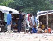 راولپنڈی: خانہ بدوش خواتین اور بچے اپنی جھگیوں کے باہر بیٹھے ہیں۔
