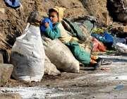 راولپنڈی: کمسن خانہ بدوش بچہ کوڑے کرکٹ کے پاس کھیل رہا ہے۔