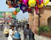 ملتان: محنت کش پھیری لگا کر گیسی غبارے فروخت کر رہے ہیں۔
