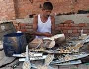 ملتان: محنت کش سڑک کنارے بیٹھا جوتے بنا رہا ہے۔
