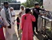 اسلام آباد: بری امام کے مزار پر آئے عقیدت مند خواتین اور بچے کولر سے ..