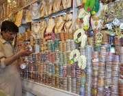 لاہور: دکاندار گاہکوں کو متوجہ کرنے کے لیے چوڑیاں سجارہا ہے۔