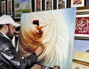 اسلام آباد: لوک میلہ 2018میں شریک ایک آرٹسٹ پینٹنگ بنا رہا ہے۔