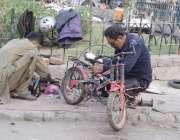 لاہور: ایک کاریگر نیلا گنبد میں سائیکل مرمت کررہا ہے۔