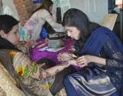 لاہور: ایک طالبہ اپنی دوست کو مہندی لگار ہی ہے۔