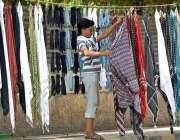راولپنڈی: محنت کش سڑک کنارے رومال فروخت کے لیے سجا رہاہے۔