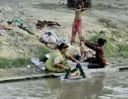 لاہور: خانہ بدوش خواتین نہر کنارے بیٹھی کپڑے دھو رہی ہیں۔