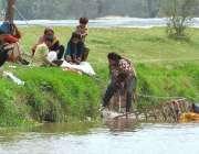 ملتان: خانہ بدوش خواتین نہری پانی سے کپڑے دھو رہی ہیں۔