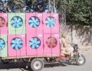 لاہور: ایک شخص رکشے پر ایئرکولر لیکر جا رہا ہے، موسم گرما کی آمد پر ایئرکولروں ..