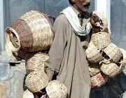 اسلام آباد: محنت کش پھیری لگا کر ہاتھ سے بنی ہوئی ٹوکریاں فروخت کررہا ..