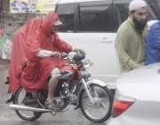 لاہور: شہر میں ہونیوالی بارش کے دوران موٹر سائیکل سوار برساتی پہنے ..