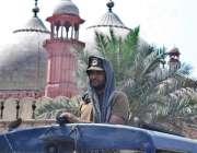 لاہور: ایک پولیس اہلکار شدید گرمی میں بادشاہی مسجد کے باہر اپنے فرائض ..