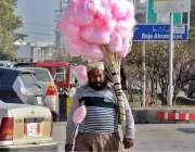 راولپنڈی: محنت کش چینی کے بنے لچھے اٹھائے فروخت کے لیے جارہا ہے۔