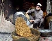 پشاور: محنت کش بھٹی پر چنے بھون رہا ہے۔