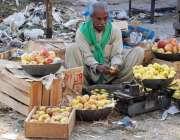 لاہور: سبزی منڈ ی میں ایک محنت کش سیب چھانٹی کر رہا ہے۔
