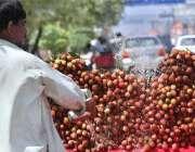 راولپنڈی: ریڑھی بان لیچی کو تازہ رکھنے کے لیے پانی کا چھڑکاؤ کر رہا ..