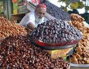 حیدر آباد: معمر دکاندار فروخت کے لیے مختلف اقسام کی کھجوریں سجا رہا ..