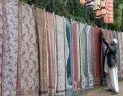 راولپنڈی: دکاندار گاہکو ں کو متوجہ کرنے کے لیے شالیں سجا رہا ہے۔